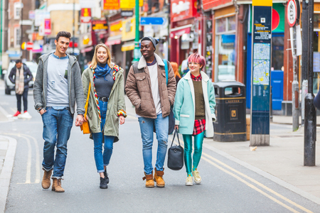 street people: Group of young friends walking in London