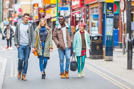 personas en la calle: Grupo de jóvenes amigos caminando en Londres