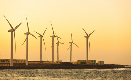 desalination: Windfarm view next to the seaside in Fuerteventura, Spain, at sunset. Wind turbines are used to power the desalination plant. Technology and ecology concepts. Stock Photo