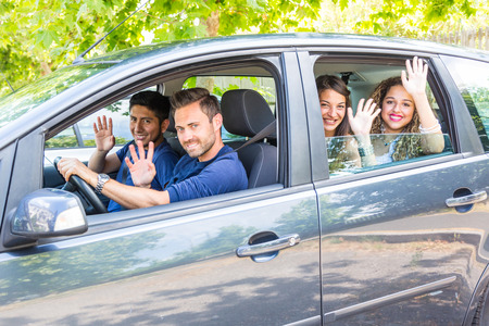 two women: Group of people in the car. They are a multicultural group of friends leaving for a trip. There are two men sitting on the front and two women on the back. They are smiling and waving their hands. Stock Photo