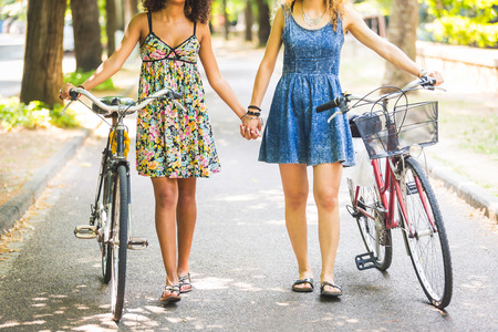 Two lesbian girls walking on the street. They are two women walking together and  holding their hands and a bike. Homosexuality and lifestyle concepts.