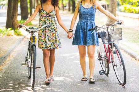 Due ragazze lesbiche che camminano per la strada. Sono due donne che camminano insieme e tenendo le mani e una bicicletta. Omosessualità e stile di vita.
