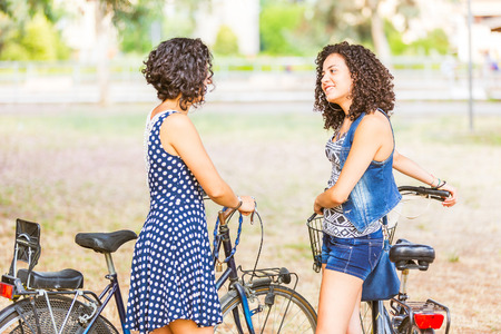 Female friends, a couple or sisters,  holding bikes and walking in the city. They are two women, they are talking and smiling. Neutral background, it could be a park or an urban square. photo