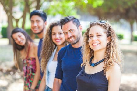 grupos de personas: grupo multicultural de amigos en el parque. Hay tres mujeres y dos hombres sonriendo y mirando a la cámara. Se trata de llevar ropa de verano. Selectivo se centran en la niña en primer plano.