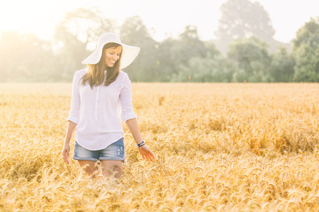 white woman: Joyful woman in the countryside walking through a wheat field. She is wearing short jeans, a white shirt and a straw hat. Relaxation and happiness concepts. Stock Photo
