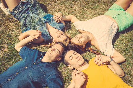 beautiful boys: Friends lying and relaxing on the grass . They are two girls and two boys resting at park, holding hands and keeping eyes closed. Beautiful image of friendship and togetherness.
