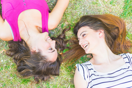 streight: Two girls lying on the grass and laughing looking each other. One has curly hair and the other has streight hair, both brunette. Relaxation and friendship concepts.