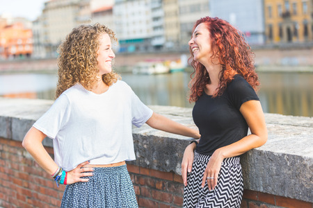 next to each other: Two girls having fun together in the city. They are standing next to a river, facing each other and laughing. They are wearing summer clothes and enjoying their time as best friends.