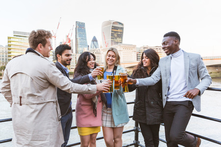 beer after work: Business group in London drinking beer after work. They all are young, smiling and wearing smart casual clothes. Mixed race group. Also could refer to a group of friends.