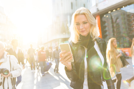 early forties: Blonde woman looking at smart phone in London at sunset. She is on her early forties, she looks candid and spontaneous. Backlight shot with blurred people on background. Stock Photo