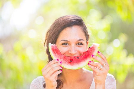 Beautiful young woman showing a slice of watermelon as a smile. She is caucasian, she wear a white dress and she has a braid on the shoulder. Summer and lifestyle concepts.