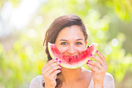 watermelon: Phụ nữ trẻ đẹp thể hiện một miếng dưa hấu như một nụ cười. Cô ấy là người da trắng, cô ấy mặc một bộ váy trắng và cô ấy có một cái áo lót trên vai. Khái niệm về mùa hè và lối sống. Kho ảnh