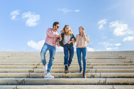 two women and one man: Multiracial group walking down a staircase and having fun in Hamburg. They are two women and one man, smiling and embracing with a blue sky on background. Friendship and lifestyle concepts.