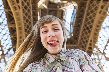 tongue out: Beautiful blonde girl taking a selfie under the Eiffel Tower in Paris. She is looking at camera, smiling and grimacing with the tongue out of the mouth. Travel and lifestyle concepts.