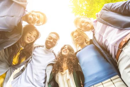 circulo de personas: Grupo de hombres de negocios abrazado en un círculo, mirando hacia abajo a la cámara. Todos ellos son jóvenes, sonriente y con ropa casual elegante. grupo de raza mixta. Trabajo en equipo y de negocios conceptos. Foto de archivo