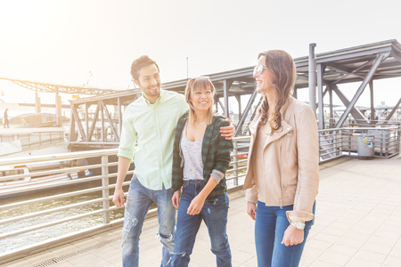 two women and one man: Multiracial group walking and having fun in Hamburg. They are two women and one man, on background there is a pier and a boat. Friendship and lifestyle concepts.