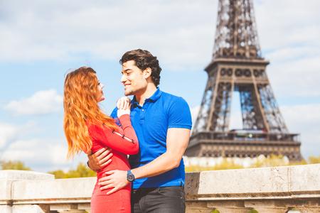 jovenes felices: Pareja en lonve en París con la Torre Eiffel en el fondo. mujer caucásica Redhead y hombre de Oriente en sus treinta años que miran el uno al otro y sonriendo. Amor y viajes conceptos. Foto de archivo