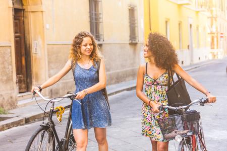 mujeres felices: pareja multirracial de amigos montando bicicletas en una calle de la ciudad. Son dos las mujeres que usan ropa de verano y que recorren en un callejón estrecho con sus bicicletas. Estilo de vida y amistad conceptos.