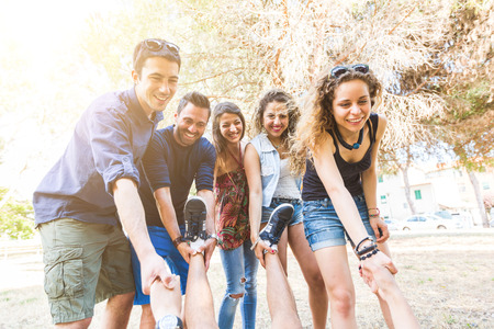 six persons: Group of friends helping someone to rise. They are looking at him and holding his hands and feet. Mixed race group. Friendship and teamwork concepts. Stock Photo