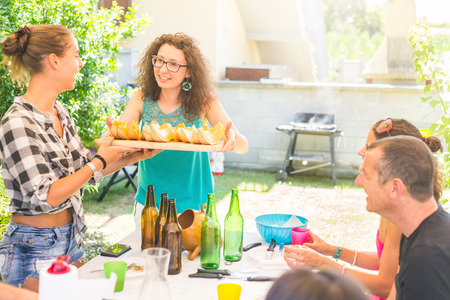 lunch tray: Woman holding a tray with slices of melon and offering to friends. They all are sitting around a table, they had lunch together on a sunny summer day. Friendship and togetherness concepts.