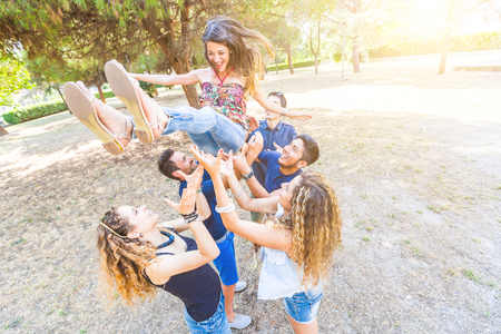 six persons: Group of friends throwing a woman in the air. They are six persons with mixed races and ethnies. Friendship, lifestyle and success concepts.