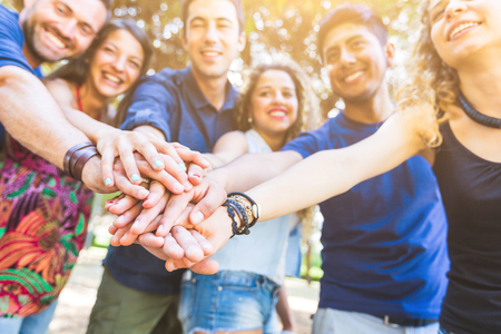 Multikulturelle Gruppe von Freunden mit den Händen auf Stapel. Sie sind sechs Personen, drei Jungen und drei Mädchen, auf ihren frühen Zwanzigern. Teamwork und Zusammenarbeit Konzepte.