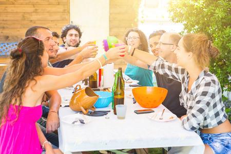 grupos de personas: Un grupo de personas que se sientan en la mesa del almuerzo que tiene. Un grupo multicultural de amigos está tostando mientras están comiendo. Ellos se divierten juntos. Todo el mundo está usando ropa de verano.