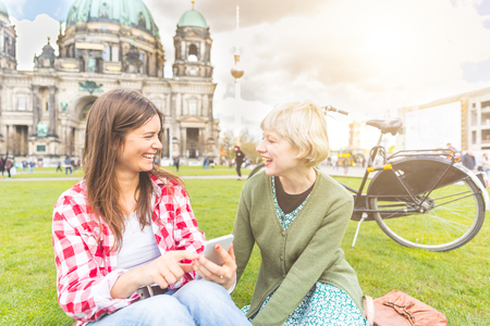 two persons only: Two young women relaxing in Berlin with the Cathedral and Fernsehturm tv tower on background. They have a smart phone and they are looking each other smiling. Friendship and lifestyle concepts.