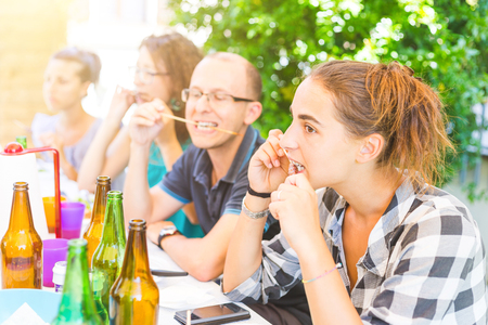 family together: Group of friends eating meat skewers on a pic nic lunch. they are sitting next to a table, having lunch and fun together. Stock Photo