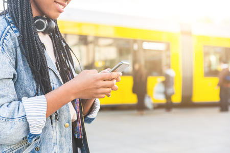afro caribbean: Black young woman typing on smart phone in Berlin. Focus on the hands holding the phone. Blurred people and tram in Alexanderplatz on background.