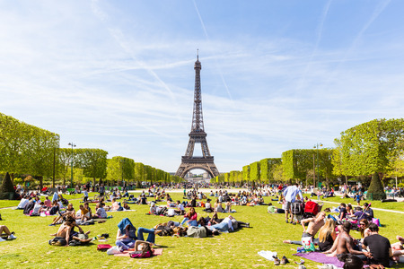 champ: PARIS, FRANCE - MAY 5, 2016: Lots of people relaxing and having fun on Champ de Mars with the Eiffel Tower on background on a sunny day.
