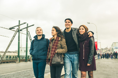 est: Group of Turkish friends walking in Istanbul on Galata bridge wearing winter clothes on a cloudy day.
