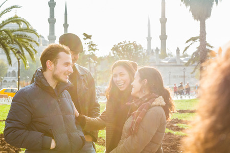 est: Group of Turkish friends in Istanbul. They are two men and two women, talking and laughing, with a mosque on background. Stock Photo