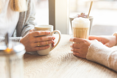 Two beautiful young women in a cafe, drinking coffee and latte macchiato. Close up shot on the hands holding the mugs.