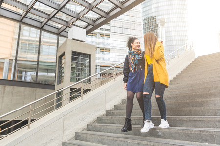 mid twenties: Lesbian couple walking in Potsdamer Platz, Berlin. Two beautiful women on their mid twenties walking and embracing. Candid situation with real people. Homosexuality and lifestyle concepts.