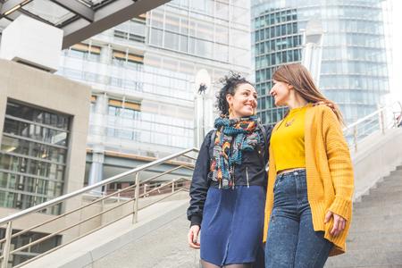 amigos abrazandose: pareja de lesbianas que camina en la Potsdamer Platz, Berlín. Dos mujeres hermosas en sus veinticinco años caminando y abrazando. situación de franca con personas reales. La homosexualidad y el estilo de vida conceptos.