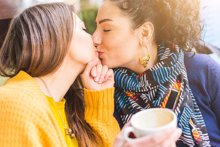 Lesbian couple kissing at a cafe. The young women are having a coffee together and give each other a passionate kiss. Candid situation with real people. Homosexuality and lifestyle concepts.