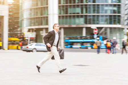 late fifties: Businessman running in the city. Blurred background with panning technique. Caucasian man on his late fifties, wearing smart casual clothes and holding a suitcase. Business and city life concepts.