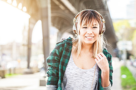 early twenties: Portrait of a beautiful young woman in Hamburg listening music. She is Japanese, on her early twenties, brunette, wearing big headphones and listening music, looking at camera and smiling.