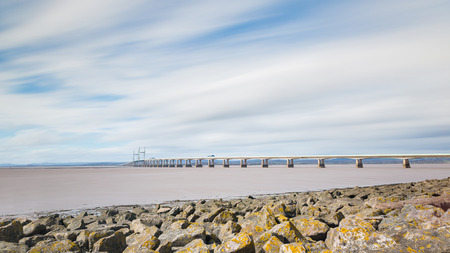 severn: Panoramic view of Second Severn crossing, a bridge linking Bristol to Wales. Long exposure image with smooth water and blurred clouds. Travel and time concepts.