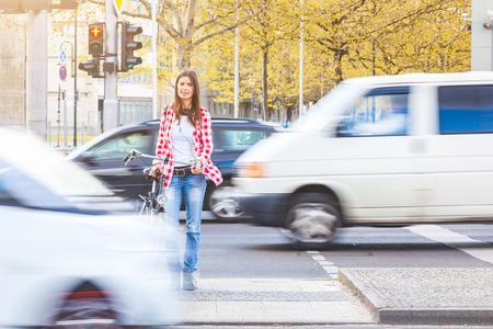 paso de peatones: Mujer joven con la bicicleta esperando para cruzar la calle en señal roja en Berlín. Hay borrosa coches que pasan delante de ella y detrás. estilo de vida y de viaje conceptos urbanos.