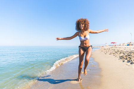 Jonge zwarte vrouw met plezier op de kust. Ze is twintig jaar oud, gemengd ras blanke en Afrikaanse zwarte, met krullend en volumineus haar, het lopen met open armen en blij gezicht.