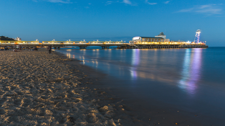 Pier in Bournemouth at night. Long exposure shot, with blurred water and people. The beach is almost empty