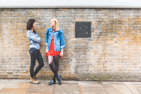 mid twenties: Two beautiful women leaning on a wall and talking in London. They are on their mid twenties, one blonde and one brunette, looking each other. Friendship and youth culture concepts. Stock Photo