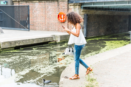hit tech: Young woman in London wandering and playing with augmented reality application on her smart phone in a dangerous way.