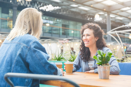mid twenties: Two women having a coffee together and enjoying life in London. They are on their mid twenties, one blonde and one brunette, looking each other and sitting at the table in a cafe. Stock Photo