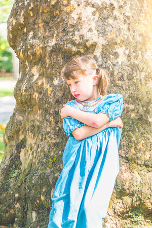 pouty: Portrait of a little girl with pouty face. An angry girl is leaning to a tree with crossed arms and looking away from camera. Tantrum, anger and loneliness concepts.