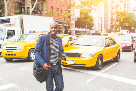 black man: Black man crossing a street in New York. Young man wearing smart casual clothes commuting in the city, with buildings and cars on background. Commuter lifestyle and youth culture concepts.