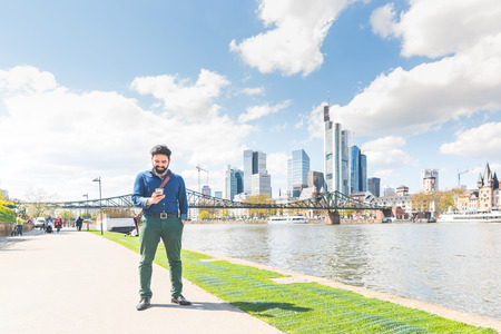 Young man typing on smart phone in Frankfurt. Middle eastern man having a walk along Main river and checking messages on the phone. City life and communication concepts