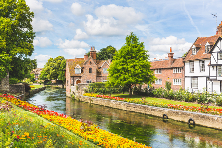 View of typical houses and buildings in Canterbury, England. Flowers and trees along the canal in summer. Postcard image on a sunny day. Architecture, nature and travel concepts. Stockfoto